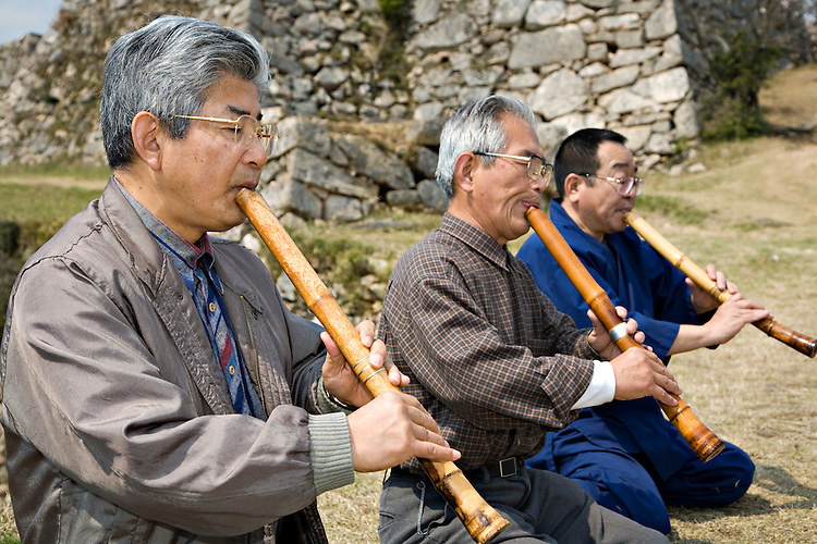 Three men playing Shakuhatchi, a traditional Japanese bamboo flute in front of Takeda Castle