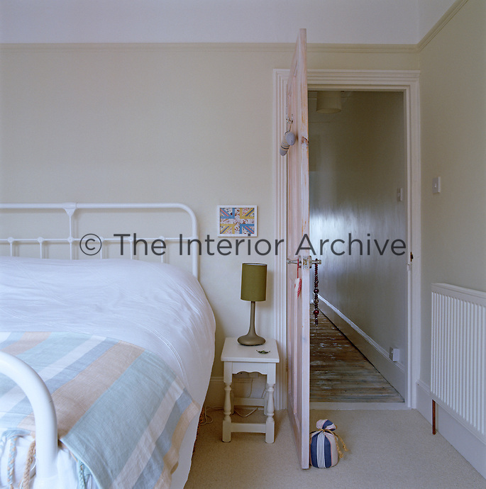 View past the wrought-iron bed in the bedroom through the open door to the corridor