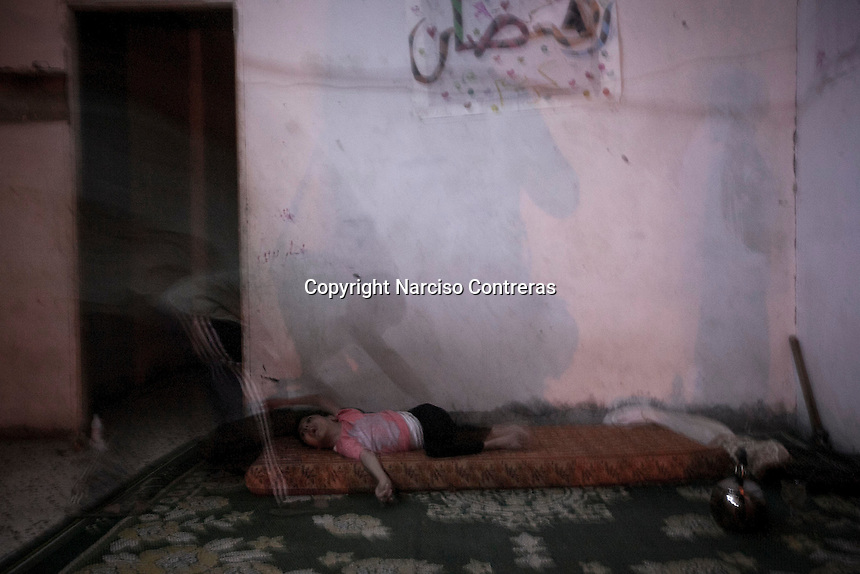 """In this Sunday, Aug. 17, 2014 photo, a Palestinian father helps to sleep to his mental disabled daughter at their partially destroyed family apartment in the Shuyaja neighborhood of Gaza City during the five days truce of the ongoing """"Protective Edge"""" Israeli military operation in Gaza Strip. (Photo/Narciso Contreras)"""