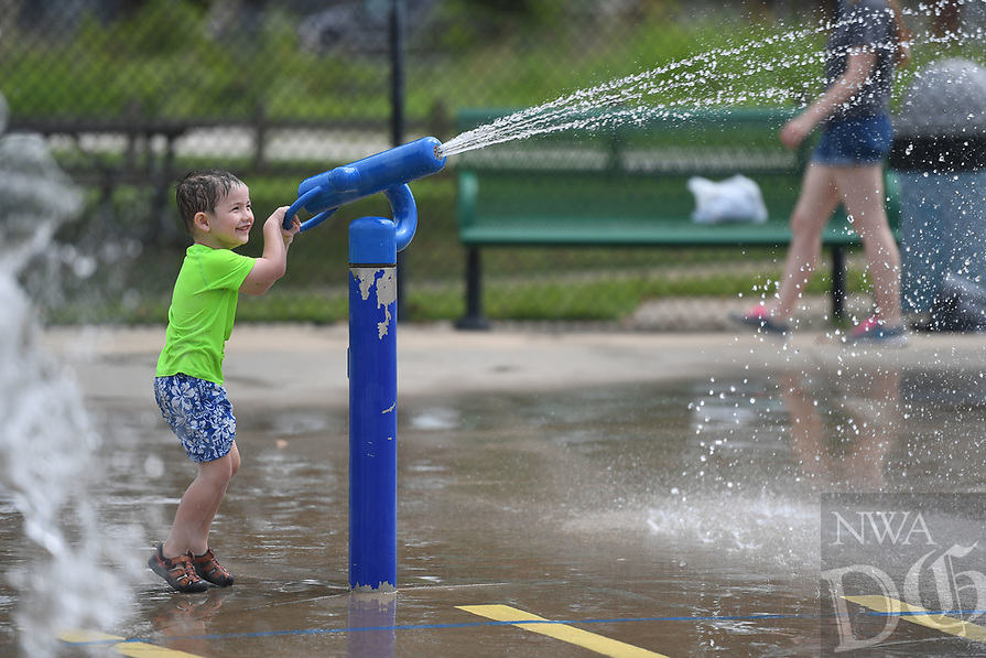NWA Democrat-Gazette/J.T. WAMPLER Eli Leis, 4, blasts a water cannon while playing Tuesday August 13, 2019 at the Rogers Splash Park. Today ((WEDNESDAY AUG 14)) is the first day of school in Rogers.