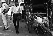 A pedestrian walks past a rickshaw puller taking an afternoon nap in Calcutta, India. 93 out of every 100 rickshaw pullers are homeless. They sleep after the city sleeps and wake up before everyone else does. Many of them are the sole bread earners for their family. Many plus 40. Many minus any other specialisation for any other job. Of the twenty four thousand rickshaw pullers, only 387 have licenses. .Many rickshaw pullers earn a meagre wage of 100-150 rupees (US $ 2.25-3.5) a day of which they have to give a daily rickshaw rent of 60 (US$ 1.35) rupees to the agent at the end of the day.