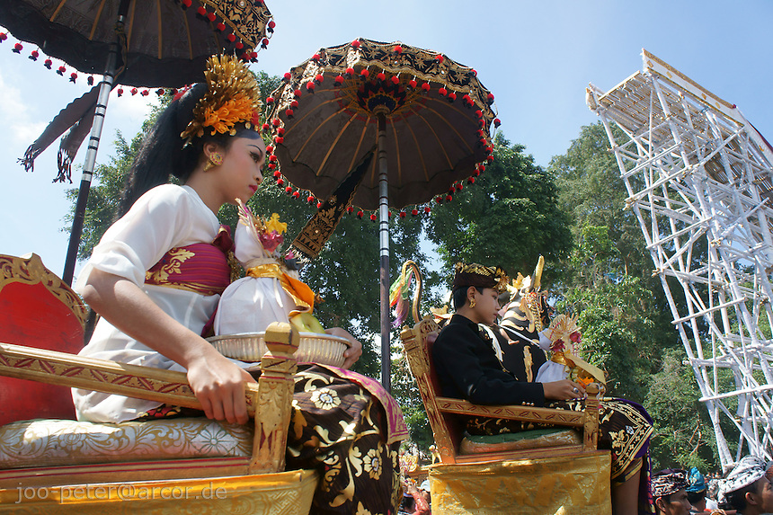 symbolic half royal, half devine  couple is carried in procession to cremation place  of  cremation of a royal family member, August 2011, Ubud, Bali, archipelago Indonesia. In the background a bamboo construction with stairs (wrapped in white cotton) where the huge tower-carriage with reminders of the passsed royal family member will dock on soon after.