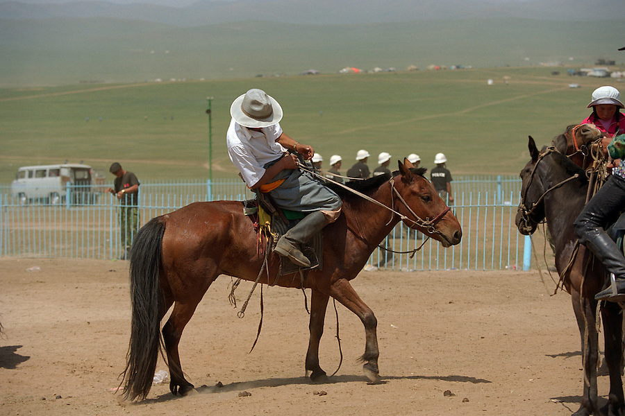 Khui Doloon Khudag, Mongolia, July 2003..Competitors & spectators at the horse racing in the national Naadam 40 kilometres outside Ulaanbaatar..A drunken horseman struggles to stay on his steed.