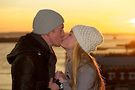 Just engaged couple kissing on Brooklyn Bridge with sunset in the background.