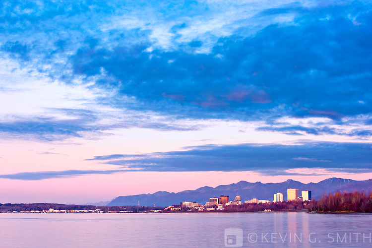 The Anchorage City Skyline reflected in the waters of Knik arm after sunset, high tide, taken from the Tony Knowles Coastal Trail, fall, Southcentral Alaska, USA.