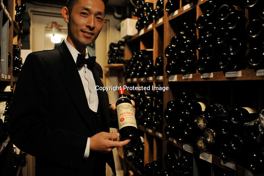 A waiter holds the popular 120,000 yen (900 euro) Petrus popualr with the Chinese in the large wine cellar of the exclusive Apicius French restaurant in the  Ginza area of Central Tokyo, 17th September, 2008.<br />