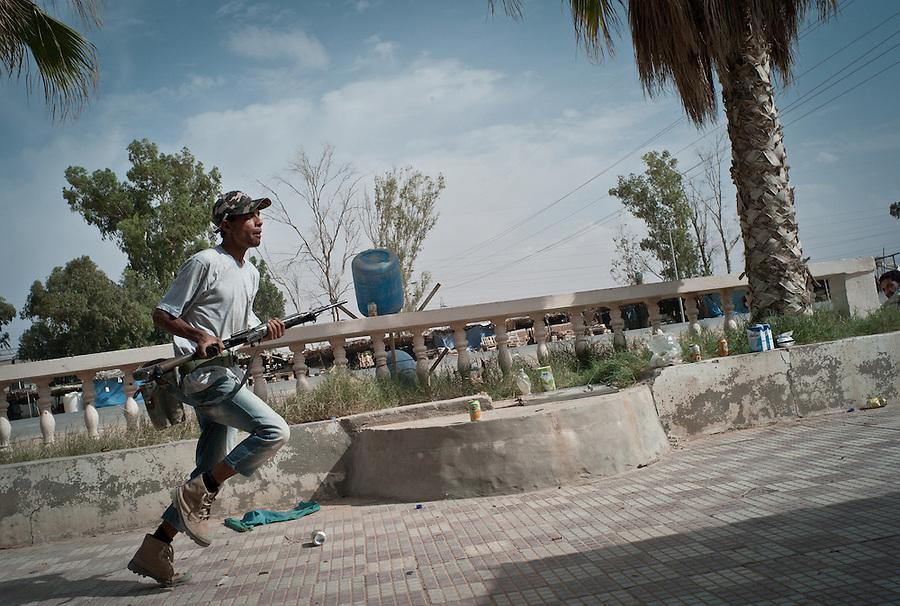Rebel fighter flees incoming fire from Gaddafi troops at the strategical crossroads to Tripoli and Zawiya near Bir Ayad, Libya.
