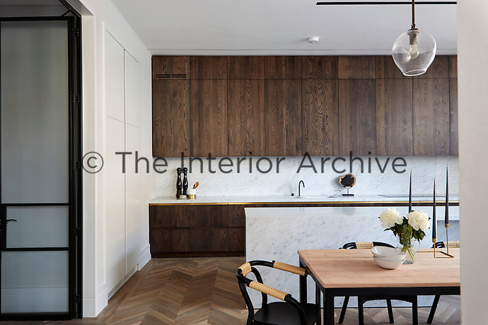In the spacious kitchen/dining room the chevron flooring is made of French reclaimed oak whilst the dining furniture has a retro feel. The bespoke joinery is subtle and unfussy and the dark wood is set off by the light grey marble.
