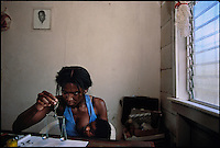 An African woman named Desiree nurses her child while weighing gold at a remote outpost in Aguyana.  She ran the business all alone because her husband (in the portrait on the wall photo) is in prison.  She shot and killed a man in a a dispute over gold.
