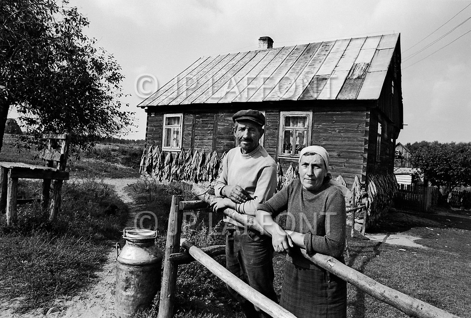 Poland, September, 1981 &ndash; Near Kolno, tobacco farmers in front of their home. Tobacco leaves are tacked to the wall of their home for drying, and a container of milk which they give to the community stands beside them.<br /> Pologne, septembre 1981 &ndash; Ces fermiers de la r&eacute;gion de Kolno, devant leur maison cultivent du tabac qui est mis &agrave; s&eacute;cher sur les murs. Leur lait ira &agrave; la communaut&eacute;.