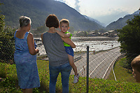 Switzerland. Canton Graubunden. Bregaglia valley. Bondo. People look at a second massive landslide while the remote village is still recovering from a huge landslide caused by a giant rockslide swept down from Piz Cengalo on August 23, 2017. The four people who had returned to their homes had to be evacuated from the village for the second time. Manuella Filli, her two boys and an elderly woman. The mudslide smash the carpentry factory and equipment that was being used to clear debris from the previous landslide. The road had to be closed to traffic. 25.08.2017 © 2017 Didier Ruef