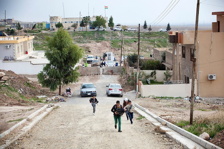 15/11/14. Alqosh, Iraq. Their day at school over, Wassam (centre, green trousers) and Milad (right, blue trousers) run for the bus that will take them back to the orphanage.