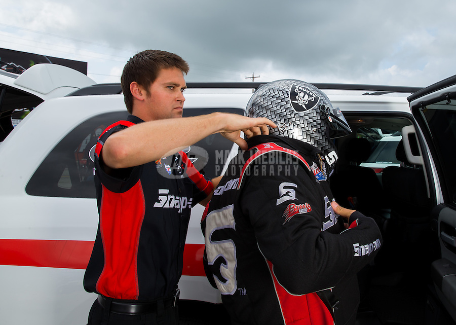 Aug 31, 2014; Clermont, IN, USA; A crew member helps NHRA funny car driver Cruz Pedregon don his safety gear during qualifying for the US Nationals at Lucas Oil Raceway. Mandatory Credit: Mark J. Rebilas-USA TODAY Sports