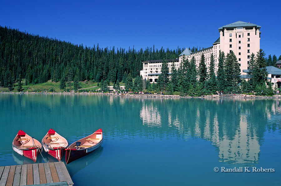 Canoes wait for tourists near the Chateau Lake Louise hotel, Lake Louise, Banff National Park, Alberta, Canada.