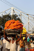 People carrying flower strings near the Howrah bridge on the banks of the Ganges River in Kolkata.<br />