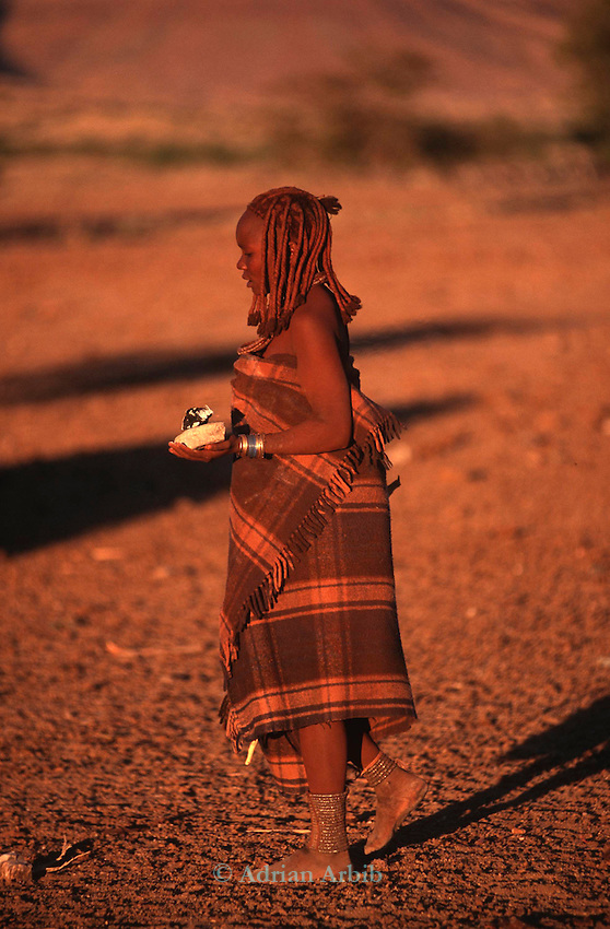 A Himba woman carrying hot coals to start a  fire. Northern Namibia.