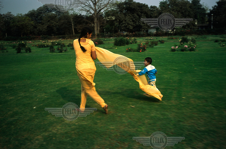A woman plays with her child in a garden in New Delhi.