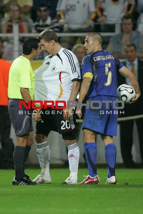 FIFA WM 2006 -  Semi Finals / Halbfinale<br /> Play    #61 (04-Juli) - Deutschland - Italien 0:2 n.V.<br /> <br /> Lukas Podolski (Mitte) von Deutschland macht Schiedsrichter Benito Archundia (MEX) (links) klar, das er am Trikot gezogen wurde. Rechts im Foto Fabio Cannavaro von Italien.<br /> <br /> Foto &copy; nordphoto