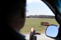 "Airport Manager Andy Jones signals to runway 27/9 from his vehicle on the runway of the Elkhart Municipal Airport in Elkhart, Indiana on April 8, 2009.  As part of the ""bail out"" funds, runway 27/9 will be repaired; Jones said he had to turn down the request from Air Force One and the president's advance staff, citing the weight of the aircraft and the fragile state of the runways, to land at Elkhart Municipal Airport."