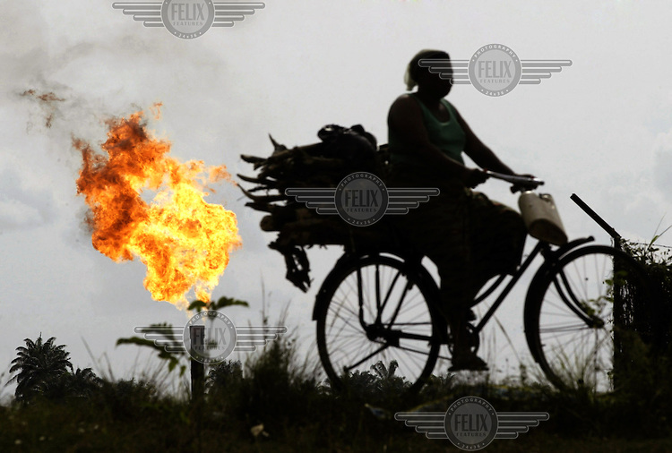 A woman carries fire wood on the back of her bicycle as she passes a burning gas flare at an Agip oil site in Ebocha.