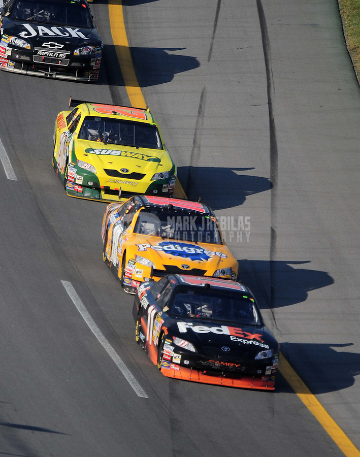 Oct 5, 2008; Talladega, AL, USA; NASCAR Sprint Cup Series driver Denny Hamlin (11) leads teammates Kyle Busch (18) and Tony Stewart (20) during the Amp Energy 500 at the Talladega Superspeedway. Mandatory Credit: Mark J. Rebilas-