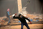 A Palestinian protester hurls stones towards Israeli security forces during clashes next to the Jewish settlement of Psagot, near the West Bank city of Ramallah, November 3, 2015. The current wave of violence erupted in mid-September, fueled by rumors that Israel was trying to increase Jewish presence in Jerusalem then quickly spread across Israel, the West Bank and the Gaza Strip. Photo by Shadi Hatem