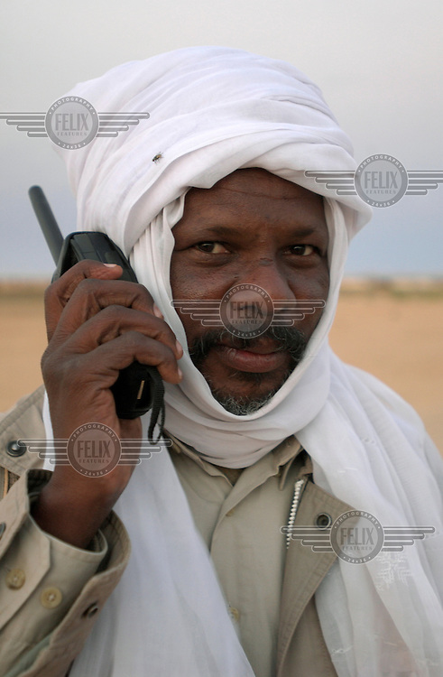 Abubakar Hamid Nour, a commander with the Justice and Equality Movement (JEM), speaks into a Thuraya satellite phone..At the point when it appeared the 20 year civil war in Sudan was nearing a conclusion a new conflict has broken out in the province of Darfur. The conflict is between black Africans, who claim the government has been oppressing them, and the local Arab population. Two rebel movements, the SLA and the JEM, have been attacking government targets. In response to this the government mobilised an Arab militia - the Janjaweed - to fight the rebels.  The militias have been accused of numerous human rights abuses and hundreds of thousands have fled their homes with at least 100,000 seeking refuge in Chad.