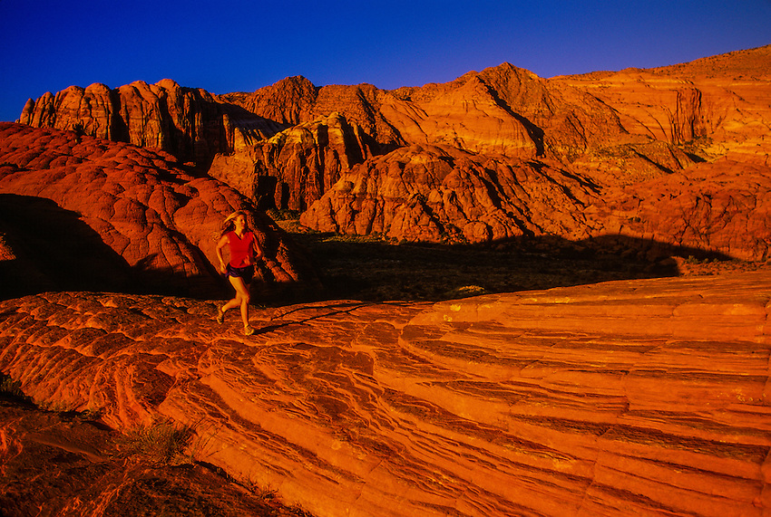 Woman running up rocks, Snow Canyon State Park, near Ivins (near St. George), Utah