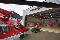 "Switzerland. Canton Ticino. Locarno Airport LSZL. The Rega base's official name is Locarno LSMO AFB (Rega 6). On a rainy day after a rescue mission, the paramedic Paolo Menghetti rides a mini tractor and pulls a Rega Agusta AW109 SP Grand ""Da Vinci"" helicopter in the base. On the left, the chopper used daily for rescue missions. On the right, a second helicopter used during a two weeks program provided as permanent staff training on a turnover basis for Rega crews from allover Switzerland. All Rega helicopters carry a crew of three: a pilot, an emergency physician, and a paramedic who is also trained to assist the pilot for radio communication, navigation, terrain/object avoidance, and winch operations. The name Rega was created by combining letters from the name ""Swiss Air Rescue Guard"" as it was written in German (Schweizerische Rettungsflugwacht), French (Garde Aérienne Suisse de Sauvetage), and Italian (Guardia Aerea Svizzera di Soccorso). Rega is a private, non-profit air rescue service that provides emergency medical assistance in Switzerland. Rega mainly assists with mountain rescues, though it will also operate in other terrains when needed, most notably during life-threatening emergencies. People in distress can call for a helicopter rescue directly (phone number 1414). As a non-profit foundation, Rega does not receive financial assistance from any government. The AgustaWestland AW109 is a lightweight, twin-engine, helicopter built by the Italian manufacturer Leonardo S.p.A. (formerly AgustaWestland, Leonardo-Finmeccanica and Finmeccanica). Leonardo S.p.A is an Italian global high-tech company and one of the key players in aerospace. In close collaboration with the manufacturer, the Da Vinci has been specially designed to cater for Rega's particular requirements as regards carrying out operations in the mountains. It optimally fulfills the high demands made of it in terms of flying characteristics, emergency medical equipment and maintenance. Safety, perf"