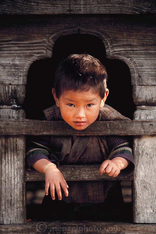 Nalim and Namgay's grandson looks out from a window in the traditional 3-story rammed earth house he shares with his large extended family. Shingkhey Village, Bhutan. From Peter Menzel's Material World Project.