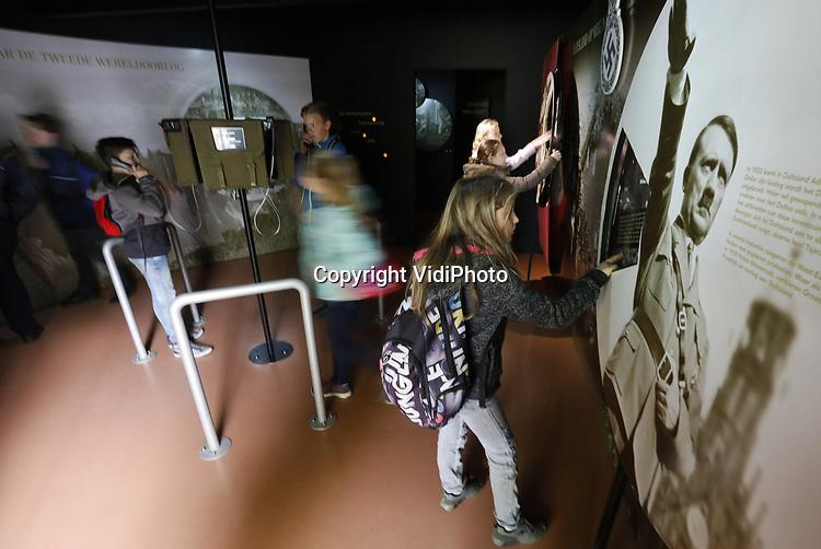 Foto: vidiPhoto<br /> <br /> RHENEN - Leerlingen van de H. J. Piekschool uit Wageningen krijgen vrijdag uitleg over de meidagen van 1940 op Ereveld De Grebbeberg in Rhenen en de bijbehorende educatieve ruimte, precies 77 jaar na de Slag om de Grebbeberg, 11-13 mei 1940. De belangstelling van scholen voor een educatieve rondleiding op de militaire begraafplaats neemt de laatste paar jaar flink toe. Volgens de gidsen op het ereveld, waar ruim 850 Nederlandse militairen uit de Tweede Wereldoorlog begraven liggen, komt dat door een hernieuwde belangstelling voor de Tweede Wereldoorlog, met name van jongeren. Op het hoogtepunt van de Slag om de Grebbeberg, 12 mei 1940, stond er een overmacht van 23.000 Duitse militairen tegenover zo'n 2500 Nederlandse soldaten. Die laatsten hadden vrijwel geen munitie en voedsel, waren nauwelijks getraind en vochten bovendien met zwaar verouderde wapens. Opmerkelijk is dat het ereveld voor de Nederlandse militairen na de capitulatie door de Duitsers is aangelegd. Zij hielden er ook de eerste herdenking voor de gesneuvelde Nederlanders.