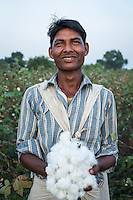 Fairtrade cotton farm labourer Kamal, 20, picks cotton in Narendra Patidar's farm in Karhi, Khargone, Madhya Pradesh, India on 12 November 2014. While his father also owns a farm, he works as a labourer in other farms when there is nothing to do in his father's farm. He earns 5 rupees per kilogram and can pick up to 40kg per day. Photo by Suzanne Lee for Fairtrade
