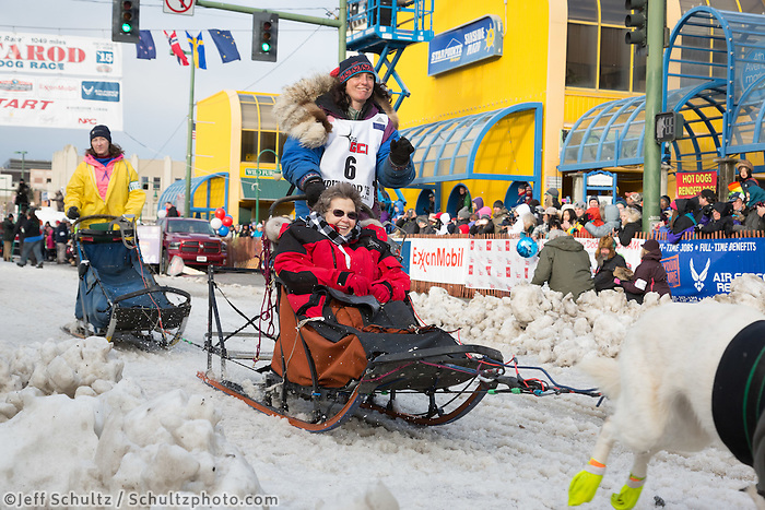 Michelle Phillips and team leave the ceremonial start line with an Iditarider at 4th Avenue and D street in downtown Anchorage, Alaska during the 2015 Iditarod race. Photo by Jim Kohl/IditarodPhotos.com