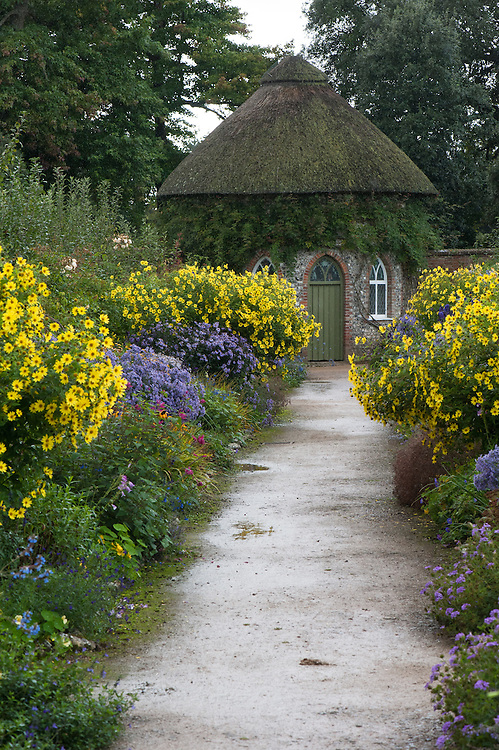 Path flanked by late summer borders featuring Asters and Helianthus, leading to the old apple store building, West Dean Garden, East Sussex, late September.