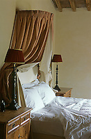Crisp white linen on a queen size bed decorated with a wall mounted canopy