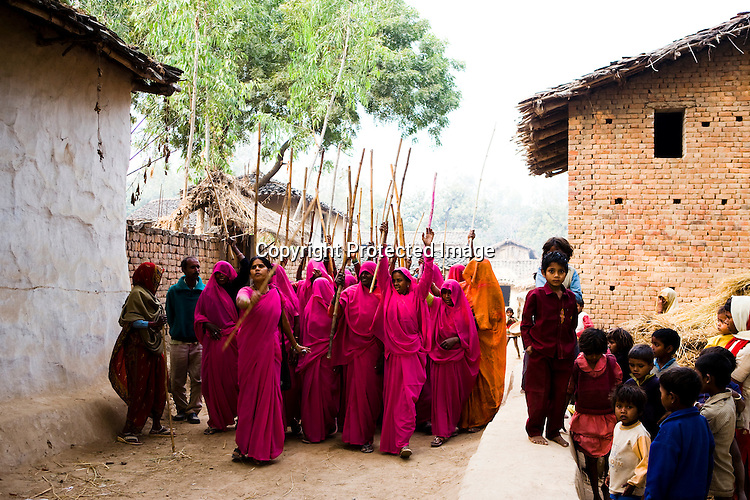 The 47-year-old leader of the Pink Gang, Sampat Pal Devi (front) is a fiesty woman. The barely educated, impoverished mother of five, Sampat Pal Devi has emerged as a messianic figure in the region. Sampath Devi began to work as a government health worker, but she quit soon after because her job was not satisfying enough. She always wanted to work for the poor and not for herself. Taking up issues while being a government worker was difficult, so she decided to quit the job and work for the rights of people...Amidst the gloom of extreme poverty, it's the colour of pink that's calling the shots in this dusty region of Bundelkhand, one of the poorest parts of one of India's northern and most populous states, Uttar Pradesh in India. A gang of vigilantes, called the Gulabi Gang (pink gang) - its 10,000 strong women members wear only pink sarees - is taking up lathi (traditional Indian cudgel) against domestic violence and corruption.