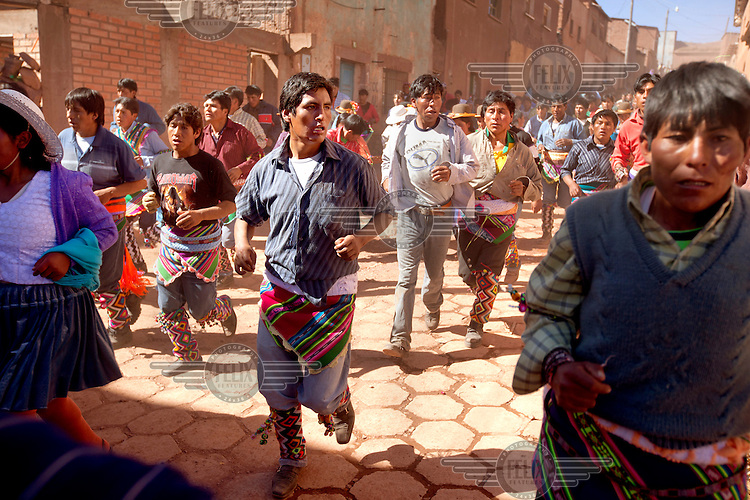 A community prepares to enter the plaza  of Macha during the tinku festival. <br /> <br /> The people of Macha and surrounding communities carry on the pre-Columbian tradition of ritual fighting. The communities gather on the plaza of Macha to fight and dance in competition with each other. The blood that is spilled is an offering to Mother Earth. In return, the people ask for rain and a good harvest. This ritual is called tinku or fiesta de la cruz since the cross is also engaged in the festivities. The cross is dressed up, given offerings and brought from communities around Macha to the church in town. This syncretic festival melds pagan, pre-christian rituals with Catholic practice. /Felix Features