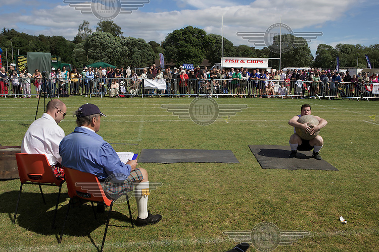 Men judge a man competing in the stone lifting event at Helensburgh and Lomond Highland games, Argyl and Bute.