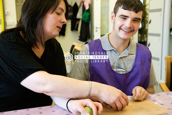 Day Service Care Assistant working with a service users with learning disabilities in an arts and crafts session,