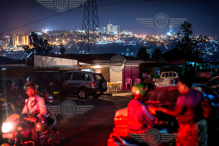 Motorcycle taxis wait for custom with Kigali's changing skyline in the background.