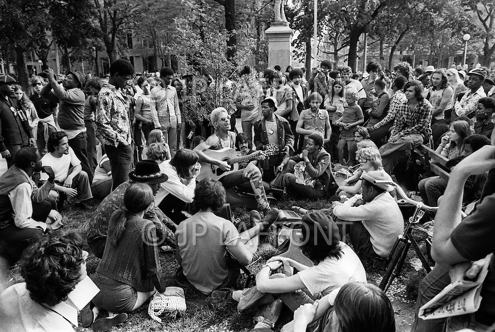 Manhattan, New York City, NY. April, 1975. <br /> Hippies listen to a man playing the guitar on a Sunday at Washington Square Park (Greenwhich Village).<br /> It is common for young americans to gather in the park and drink lots of alcohol, and smoke marijuana.