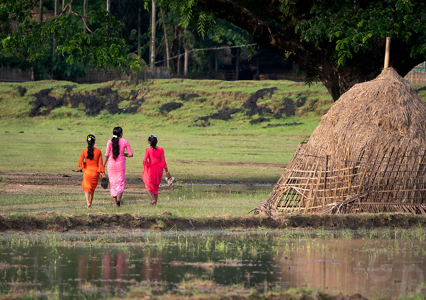 Colourful dressed girls walking in the rural area near their village, Rakhine State, Myanmar