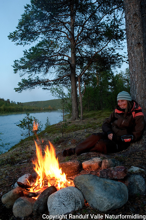 Dame slapper av foran furubål. ---- Woman relaxing in front of camp fire.