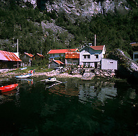Rowing small boat away from wooden clapboard summer cottage. Norwegian Fjords, Norway, circa 1976.