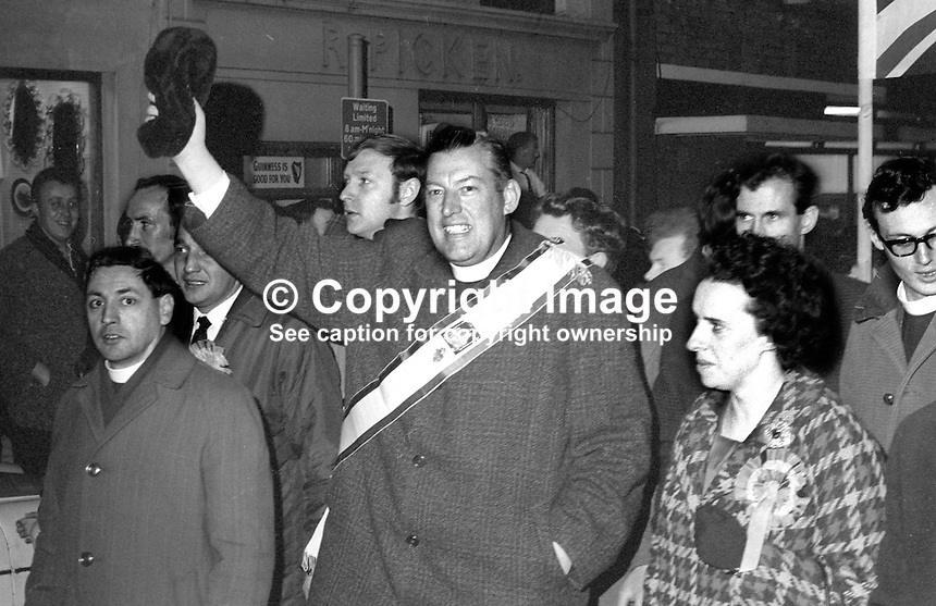 A jubilant Rev Ian Paisley, accompanied by his wife, Eileen Paisley, waving his signature astrakhan headgear following his success in the Bannside by-election on 16th April 1970 caused by Terence O'Neill's elevation to the peerage and his resignation as Northern Ireland's prime minister. The count took place in the Town Hall, Ballymena, Co Antrim. 197004160113k<br />