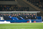 The home team's substitutes concentrate on keeping warm in the sub-zero temperatures as Hertha Berlin take on Sporting Lisbon in the Olympic Stadium in Berlin in a UEFA Europa League group match. Hertha won the match by 1 goal to nil to press to the knock-out round of the cup. 2009/10 was the the first year in which the Europa League replaced the UEFA Cup in European football competition.