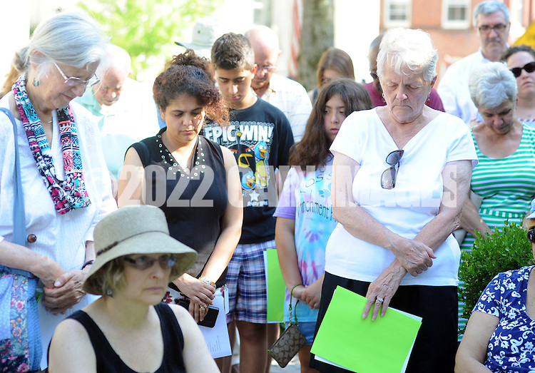 Participants bow their heads in prayer during an interfaith prayer vigil at the Bucks County Courthousein memory of the victims of the South Carolina shooting Monday June 22, 2015 in Doylestown, Pennsylvania. (Photo by William Thomas Cain)