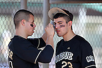Barrett Serrato #23 of the Purdue Boilermakers gets help putting on eye black from Tyler Spillner #44 during a game vs the Pittsburgh Panthers at the Big East-Big Ten Challenge at Walter Fuller Complex in St. Petersburg, Florida;  February 20, 2011.  Purdue defeated Pitt 5-3.  Photo By Mike Janes/Four Seam Images