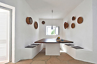 The walls of the minimal dining area are decorated with a collection of traditional Sardinian baskets