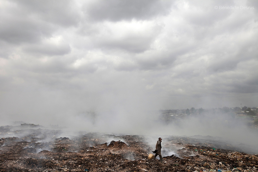 13 february 2013 - Dandora dumpsite, Nairobi, Kenya - A Kenyan scavenger looks for metal scraps exposed by waste burning and methane fires at the edge of the Dandora dumpsite, one of the largest and most toxic in Africa. This activity can be lucrative for the scavengers, but the fires cause severe diseases. A study by the Nairobi-based U.N. Environment Programme (UNEP) found that half of 328 children tested around the site suffered from respiratory problems and had lead concentrations in their blood exceeding the internationally accepted level. Located near slums in the east of the Kenyan capital Nairobi, the open dump site was created in 1975 and covers 30 acres. The site receives 2,000 tonnes of unfiltered garbage daily, including hazardous chemical and hospital wastes. It is a source of survival for many people living in the surrounding slums, however it also harms children and adults' health in the area and pollutes the Kenyan capital. Photo credit: Benedicte Desrus